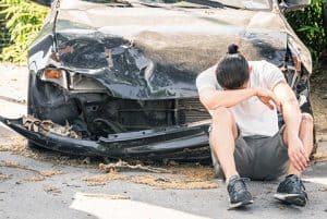 איש יושב על הכביש ומרכין ראש שמאחוריו רכב שעבר תאונה